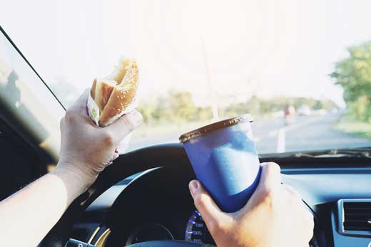 Distracted driver in a vehicle with a blue travel mug and sandwich in hand