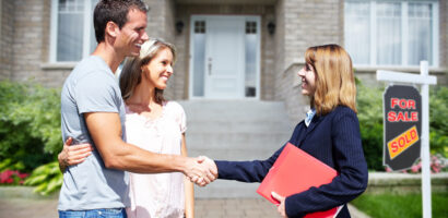 Happy couple shakes hands with a real estate agent in front of their newly purchased home