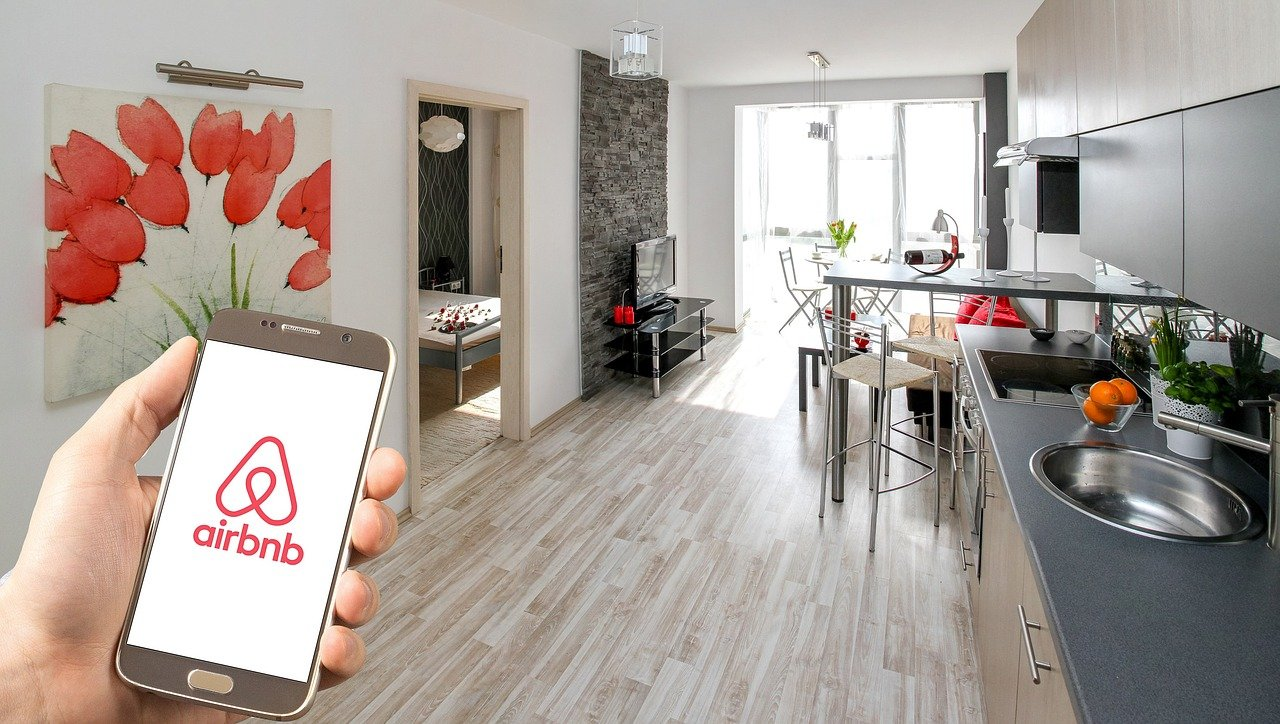 Person holding phone with AirBnB app in condo living area