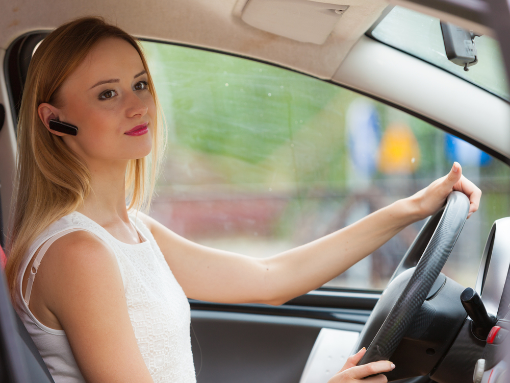 Young woman drives car safely using bluetooth ear piece for hands-free phone calls