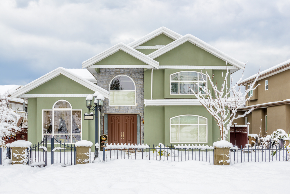 Green home with wrought iron fence covered in snow for the winter