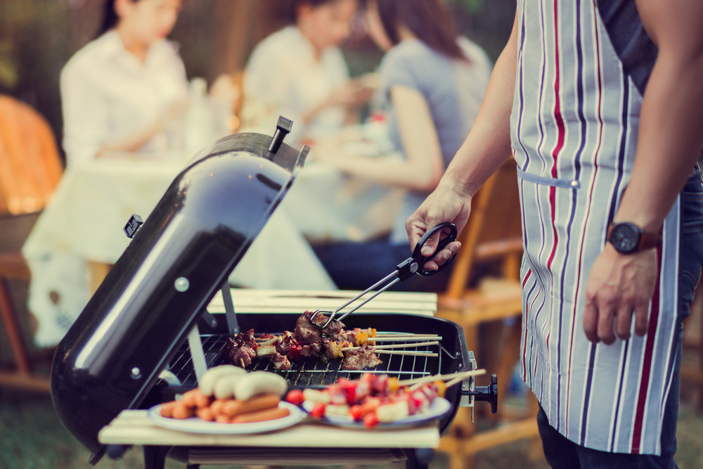 man barbecuing on a hot summer day
