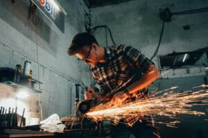 Man in plaid shirt using angle grinder on a piece of metal in dark shop