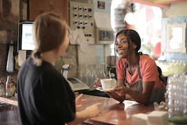Female barista serves customer a white mug of coffee over a wooden countertop