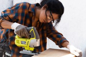 female contractor in blue and orange plaid shirt cutting plywood with a power saw