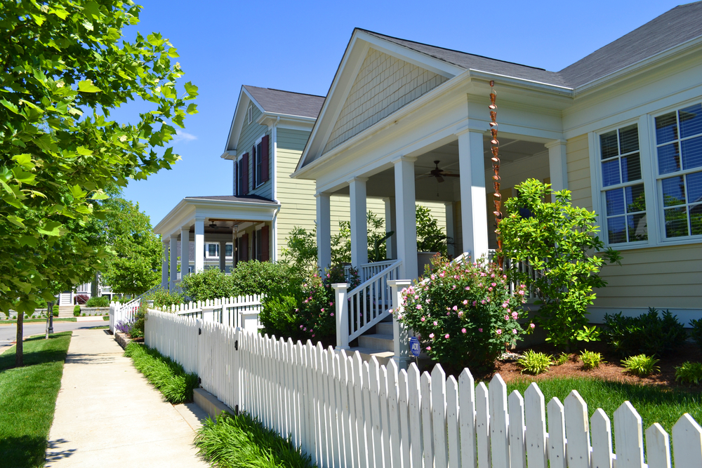 Yellow house with front porch and white picket fence