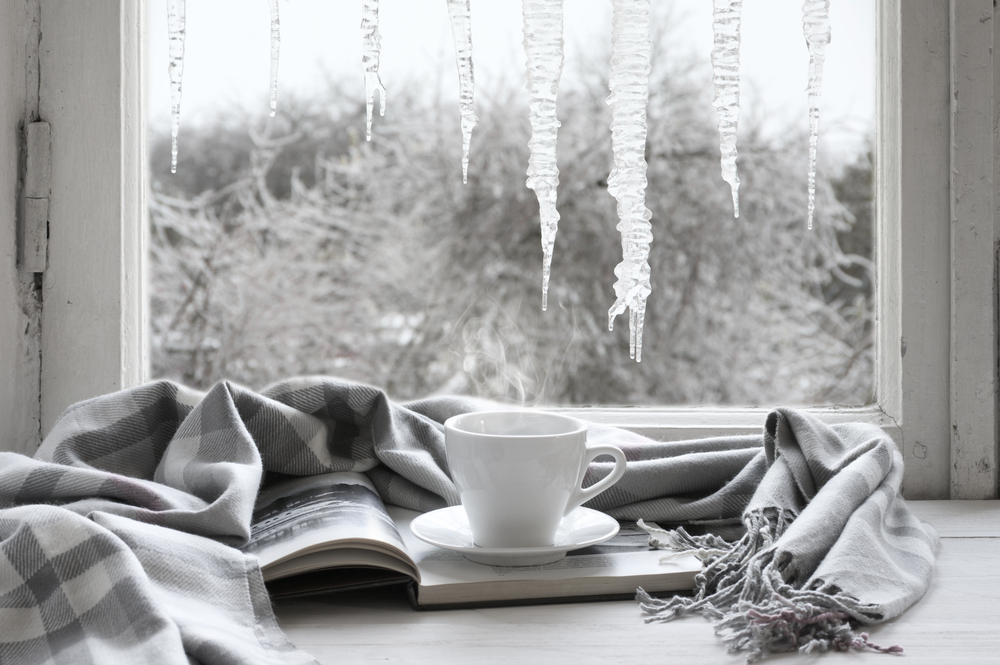 White mug on top of book wrapped in a grey blanket, with a wintery window scene in the background