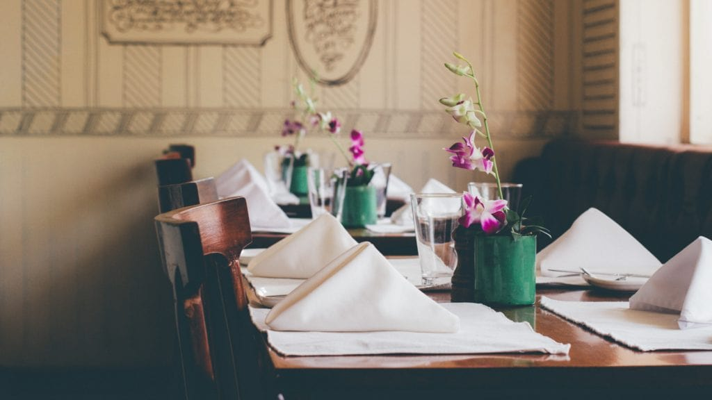 purplue-flowers-and-napkins-sitting-on-a-wooden-restuant-table