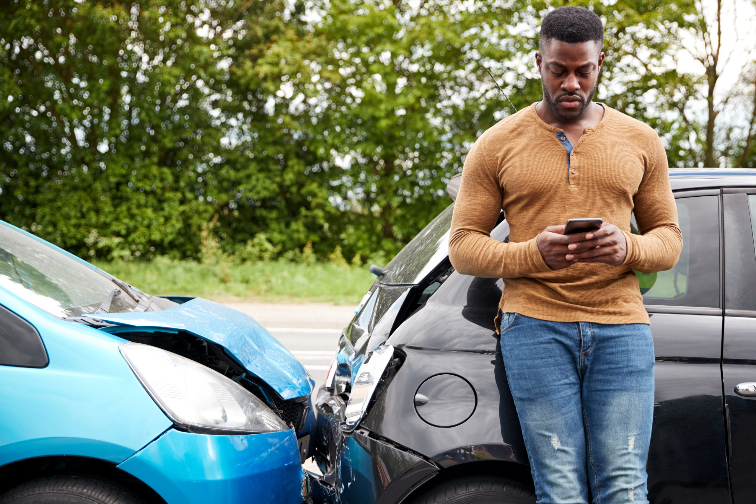 Person on a phone leaning against a car after getting into an accident