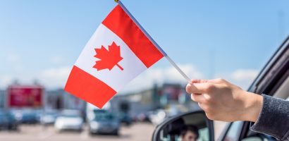 Person hanging a Canadian flag out of a car window